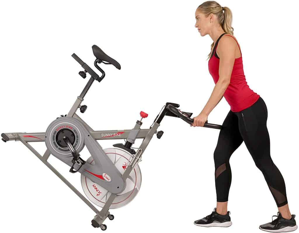 A lady moves the Sunny Health & Fitness Synergy SF-B1879 Indoor Cycling Bike for storage