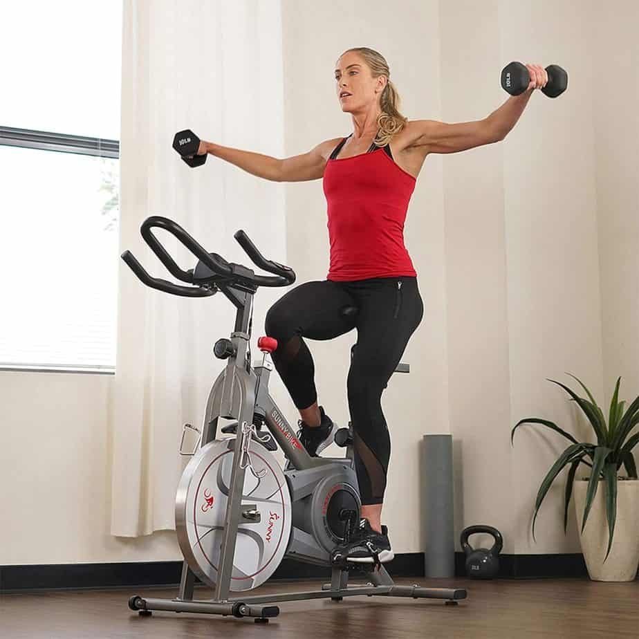 A lady workouts with the Sunny Health & Fitness Synergy SF-B1879 Indoor Cycling Bike while using dumbbells