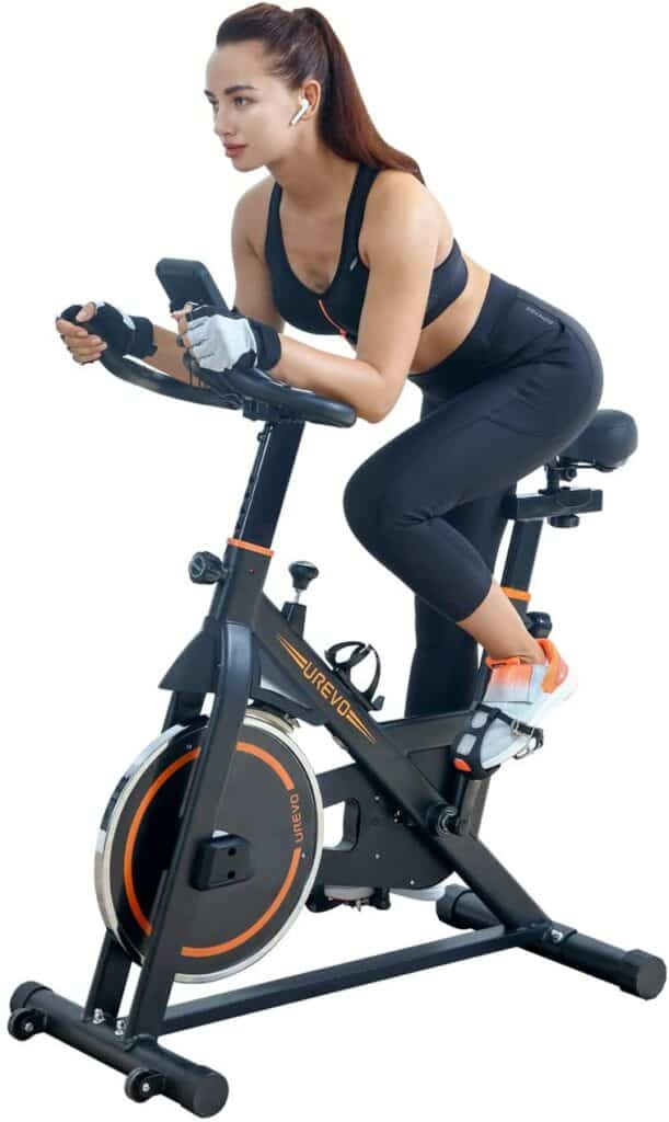 A lady exercises with the UREVO Belt Drive Indoor Cycling Bike in a racing position