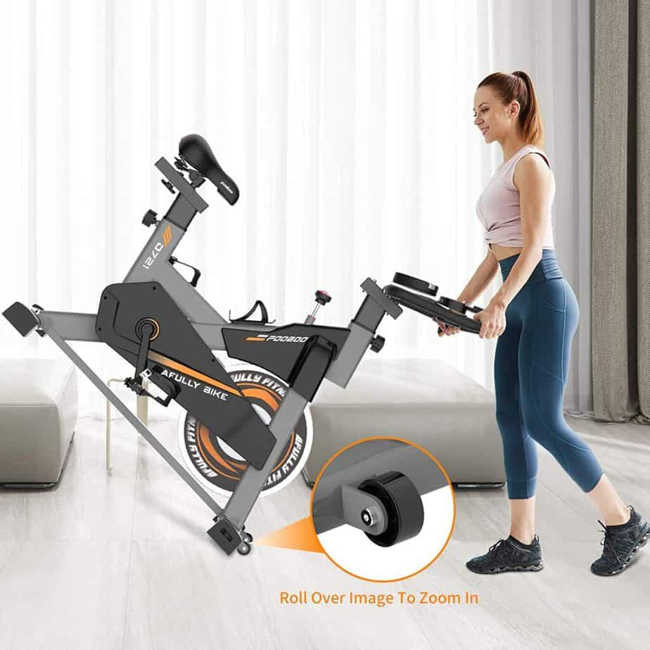 A user rolls the Pooboo S2 D721 Indoor Cycling Bike away for storage