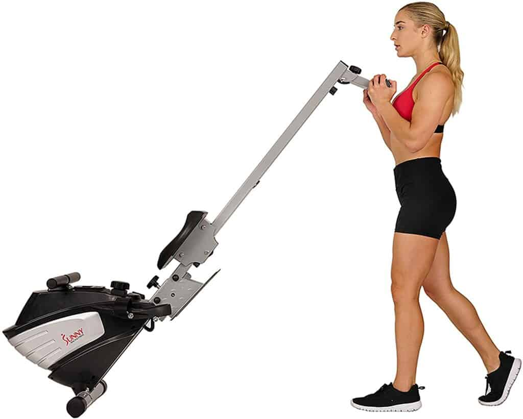 A lady moves the Sunny Health & Fitness SF-RW5622 Magnetic Rowing Machine for storage
