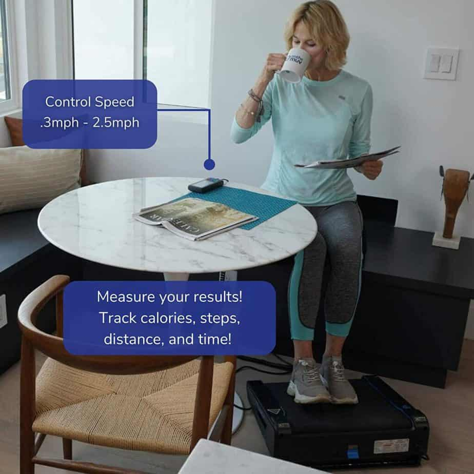 A lady uses the Onthemuv MiniTREAD Compact Electric Treadmill while sitting and enjoying a cup of tea