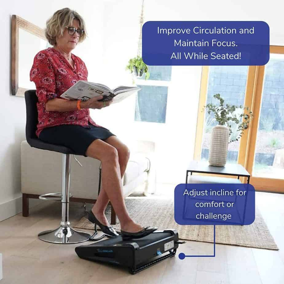 An elderly lady sits and reads a book while using the Onthemuv MiniTREAD Compact Electric Treadmill