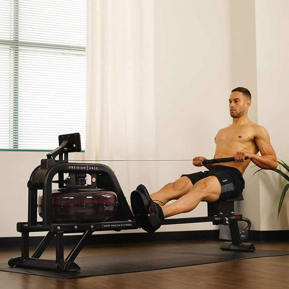 A gentleman works out with the Sunny Health & Fitness SF-RW5713 Obsidian Surge 500 Rowing Machine