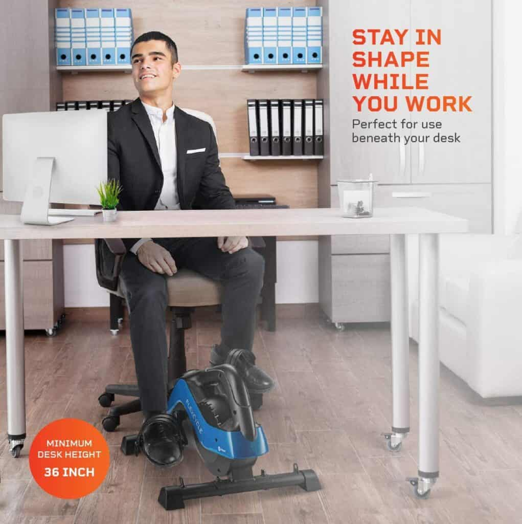 A man uses the LifePro FlexCycle Exercise Bike under a desk while working