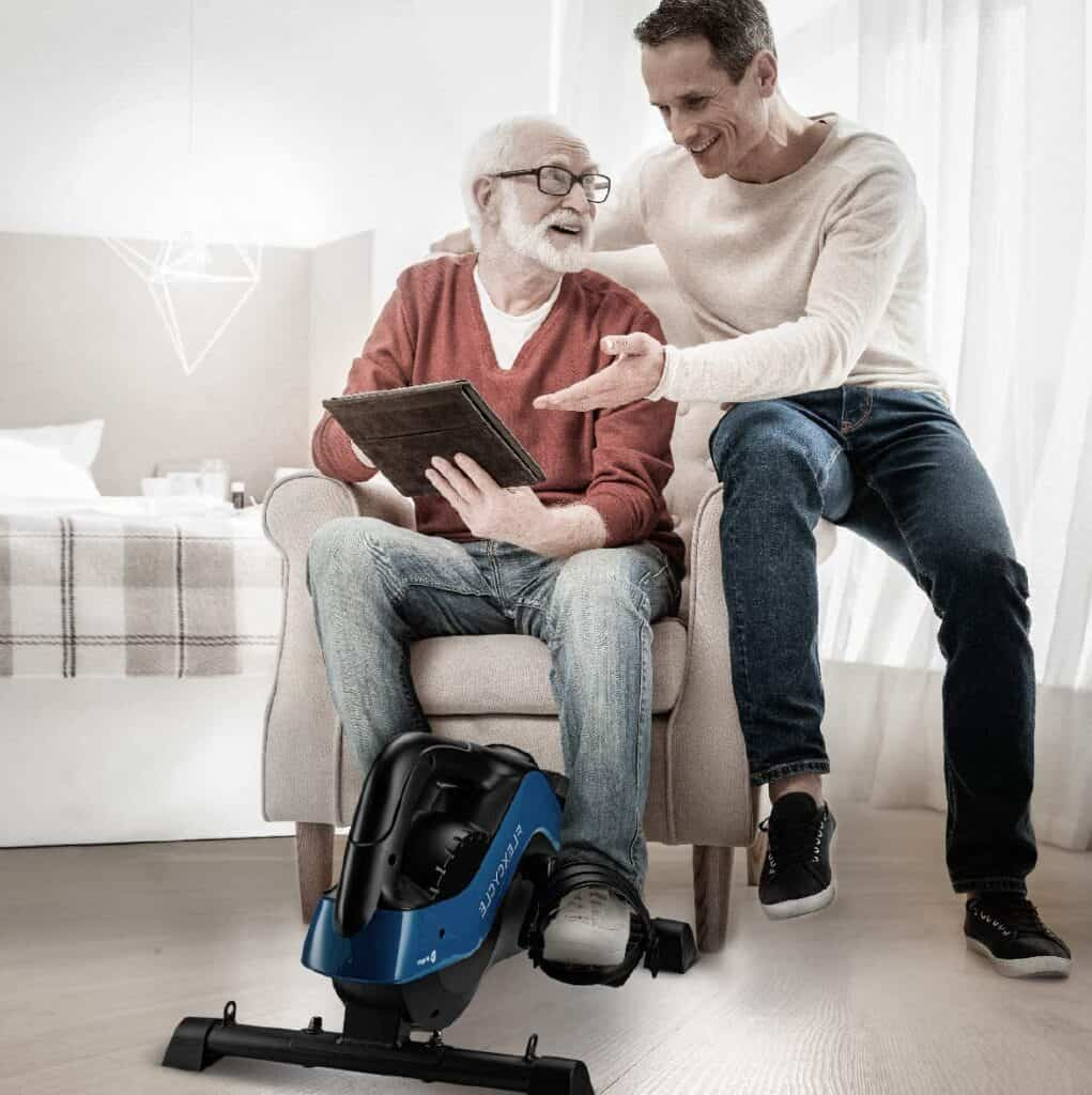 An elderly man workouts with the LifePro FlexCycle Exercise Bike while seated on a sofa