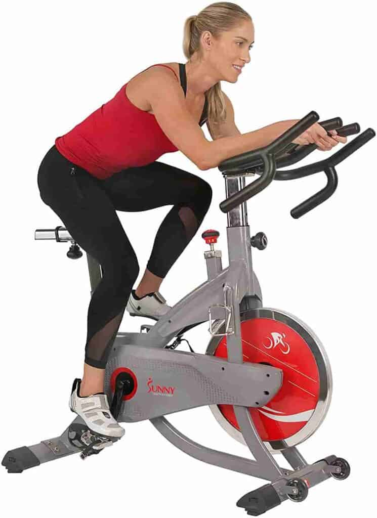 A lady rides the Sunny Health & Fitness SF-B1711 AeroPro Indoor Cycling Bike