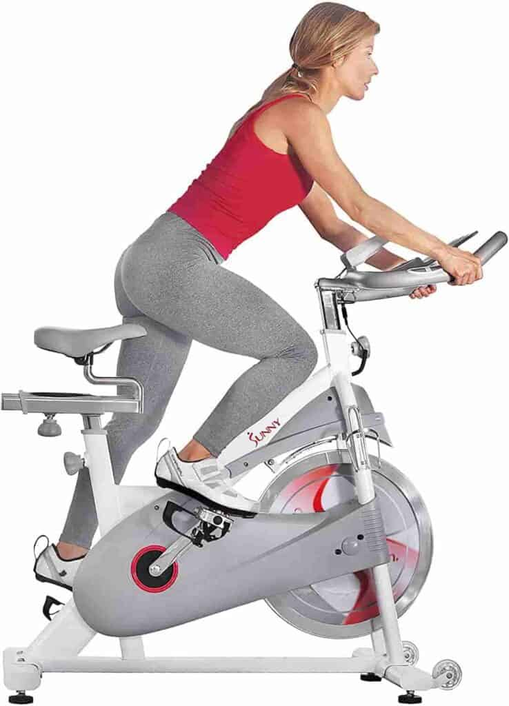 A lady rides the Sunny Health & Fitness SF-B1876 Magnetic Resistance Cycling Bike