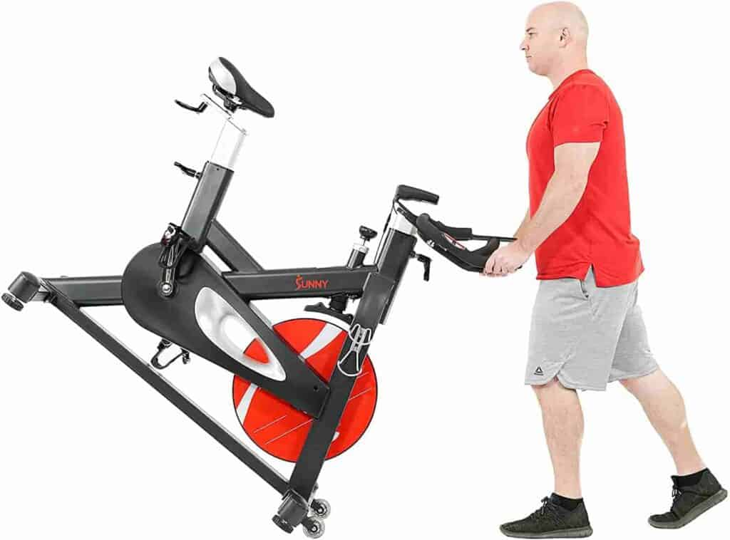 The  user rolls the Sunny Health & Fitness SF-B1986 Evolution Pro II Cycling Bike away for storage