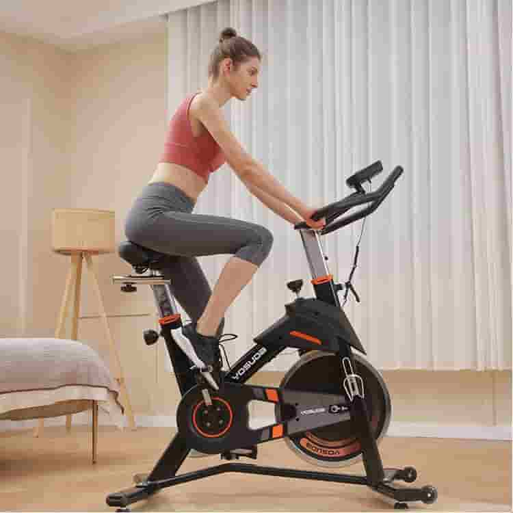 A lady rides the YOSUDA L-007A Exercise Indoor Cycling Bike