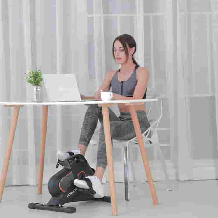 A lady uses the YOSUDA YBM-1 Under Desk Cycling Bike while working on her computer